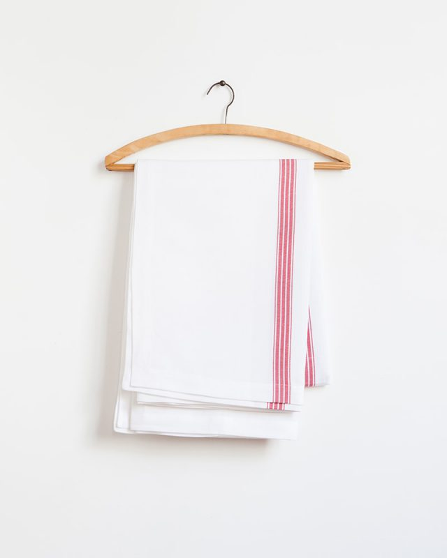 The Mungo Linen Provincial Stripe Table Cloth in White and Red displayed on a wooden hanger. Made from all natural fibres at our mill in Plettenberg Bay.