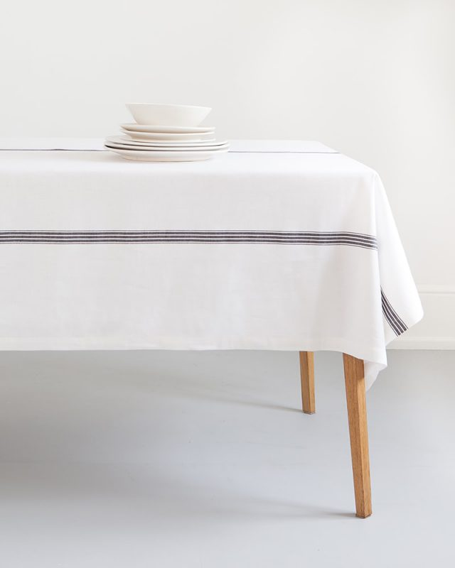 The Mungo Linen Provincial Stripe Table Cloth in French Navy paired with white crockery for a crisp table setting.