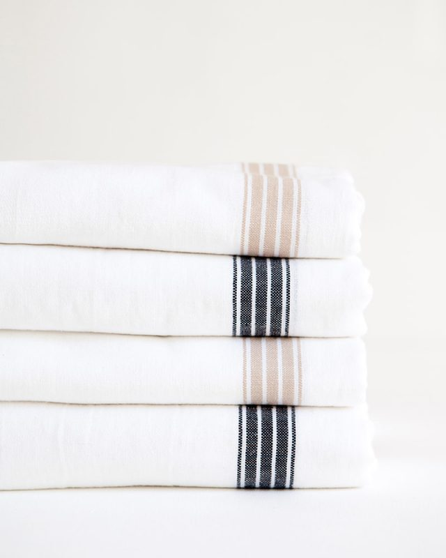 Mungo Linen Provincial Stripe Table Cloths in Natural and French Navy Stripe, folded and stacked. Made with all natural fibres at our milll in Plettenberg Bay.