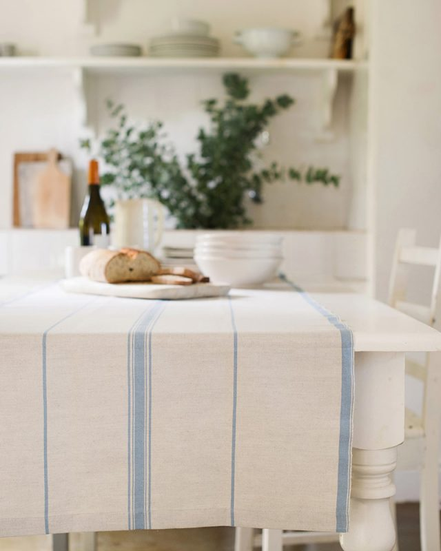 The Mungo Lisburn Linen Table Cloth in Blue Bell set on the table of a country kitchen.