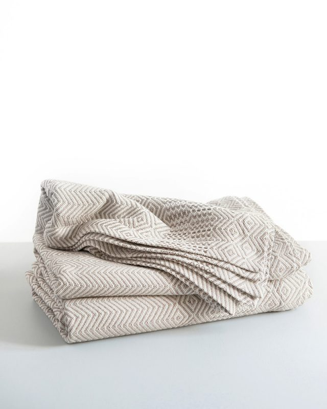 Stack of Mungo Cotton Bakuba Throws in Dune. Textile woven with all natural fibres at our mill in Plettenberg Bay, South Africa.