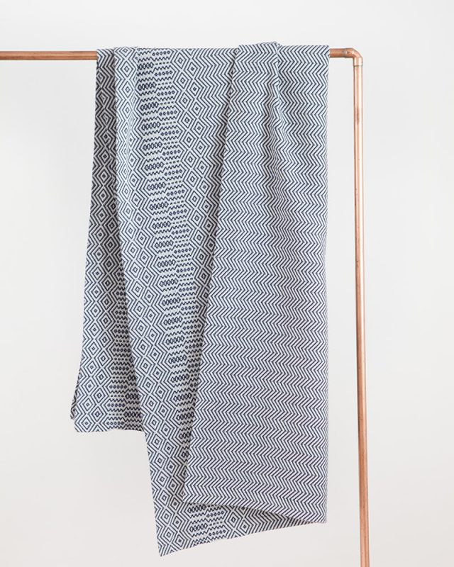 Mungo Cotton Bakuba Throw in Midnight hanging on a rail. Textile woven with all natural fibres at our mill in Plettenberg Bay, South Africa.