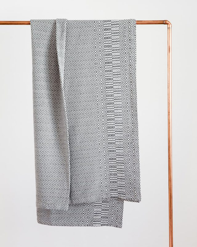 Mungo Cotton Bakuba Throw in Charcoal hanging on a rail. Textile woven with all natural fibres at our mill in Plettenberg Bay, South Africa.