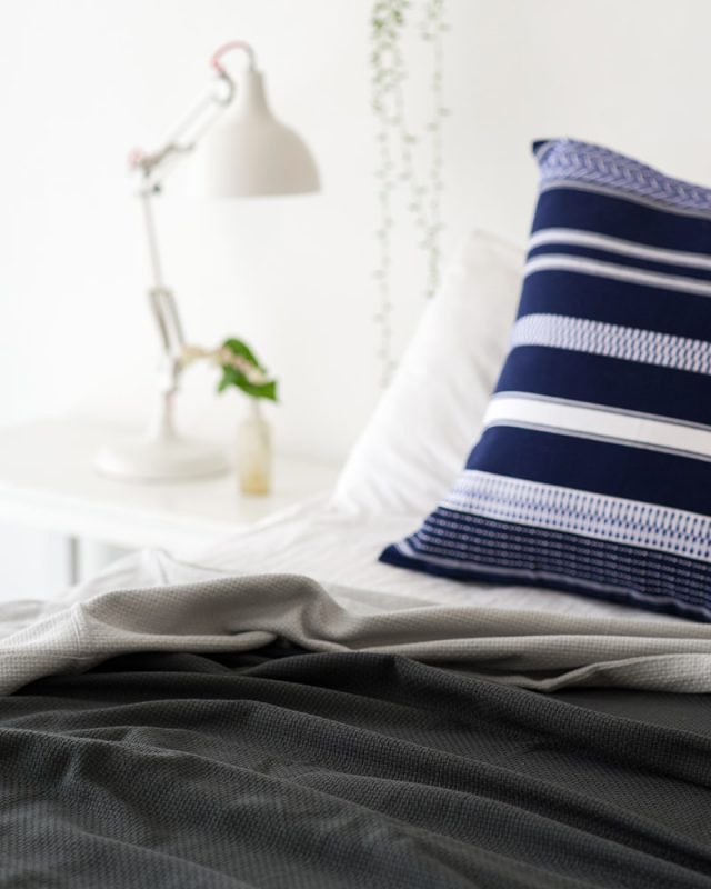 Mungo Mali Cushion in Cobalt, paired with a cotton Interlace bedcover on a bed