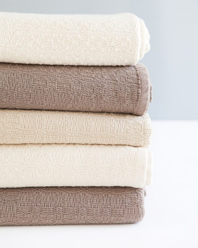 A stack of Mungo Cottonfields Cotton Blanket Throws in brown, stone and natural, textiles woven with all natural fibres at our mill in Plettenberg Bay, South Africa.
