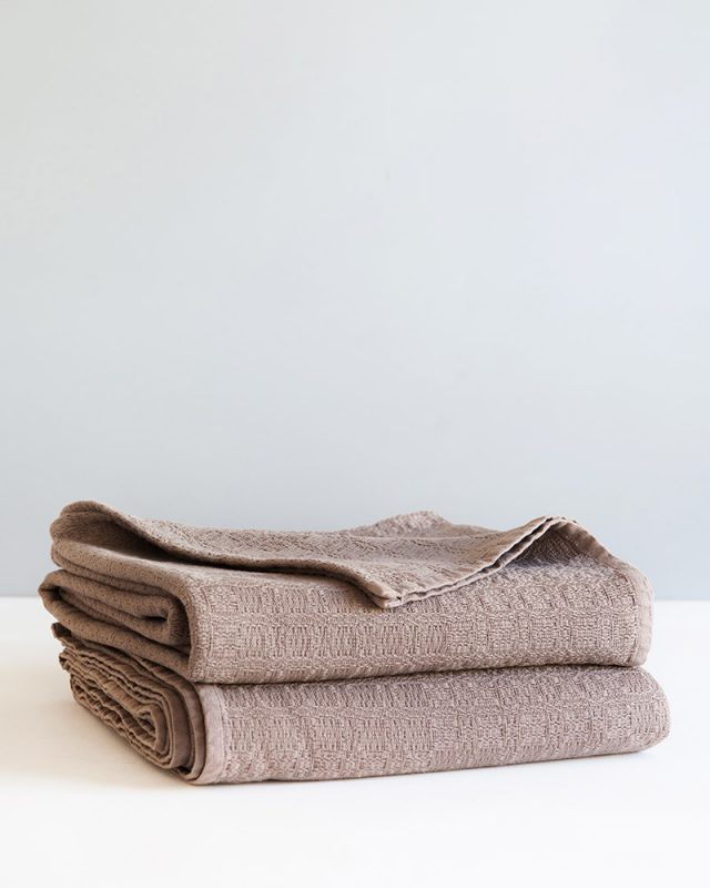 A stack of Mungo Cottonfields Cotton Blanket Throws in brown, a textile woven with all natural fibres at our mill in Plettenberg Bay, South Africa.