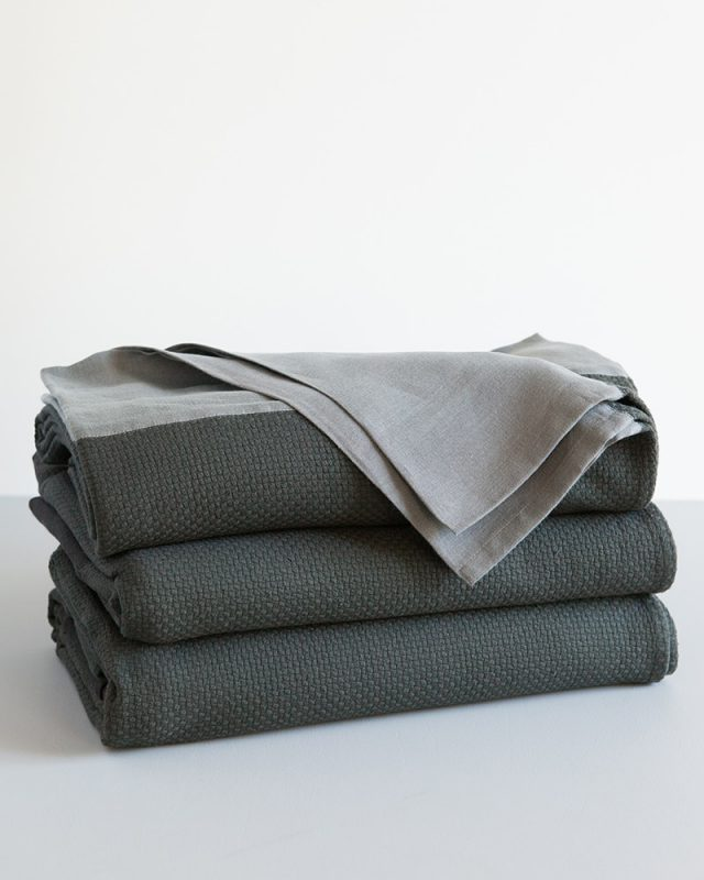 A stack of Mungo Interlace Blanket Cotton and Linen Throws in Charcoal and Metal Grey, a textile woven with all natural fibres at our mill in Plettenberg Bay, South Africa.
