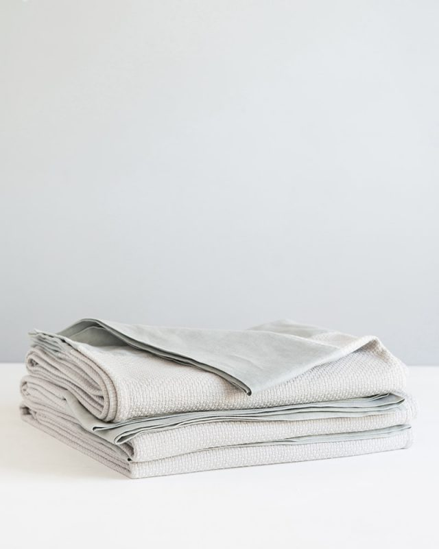 A stack of Mungo Interlace Cotton Blanket Throws in Moon Grey, a textile woven with all natural fibres at our mill in Plettenberg Bay, South Africa.