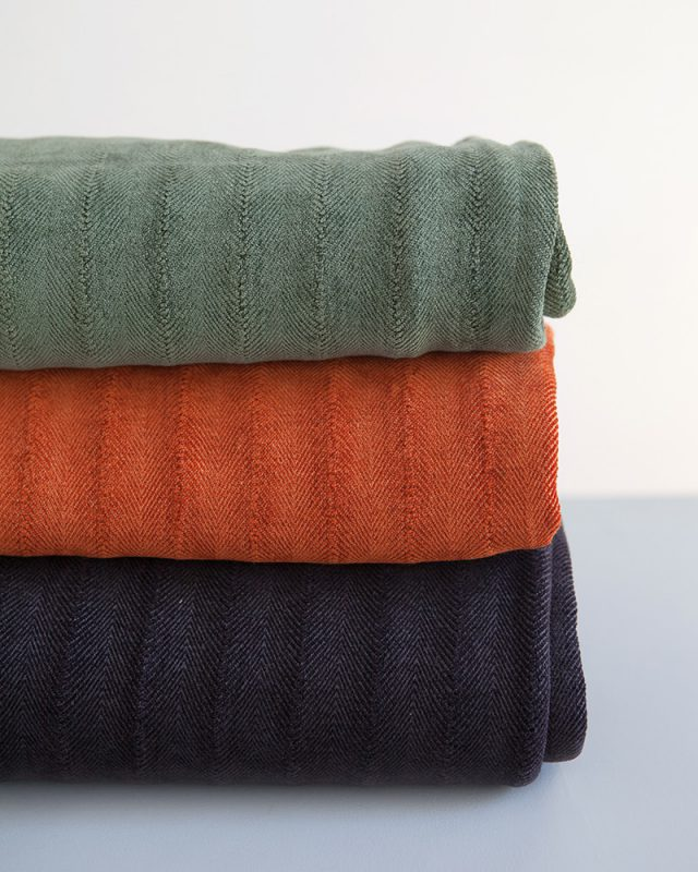 Mungo Undulating Herringbone Cotton And Viscose Chenille Throws in Urban Green, Midnight Mole and Namib Orange.