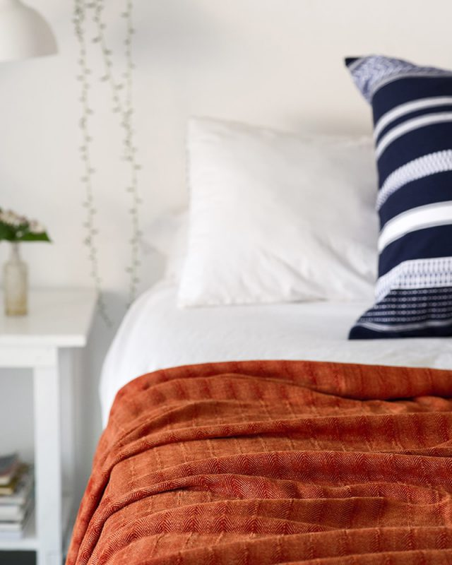 The vibrant Chenille Herringbone in Namid Orange ads a pop of colour to a minimalist bedroom featuring the Mungo Kamma Linen bedding in white.