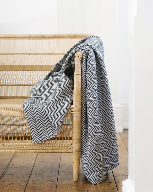 Mungo Cotton Bakuba Throw in Charcoal draped over a chair. Textile woven with all natural fibres at our mill in Plettenberg Bay, South Africa.