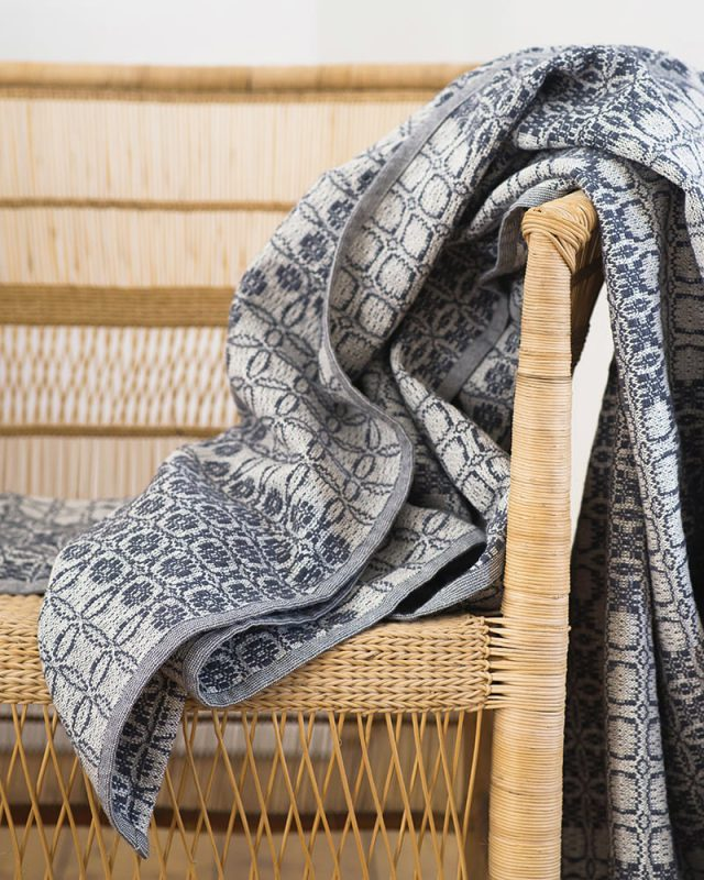 A Mungo Juno Cotton Blanket Throw in French Navy, pictured here draped over a chair, is a textile woven with all natural fibres at our mill in Plettenberg Bay, South Africa.