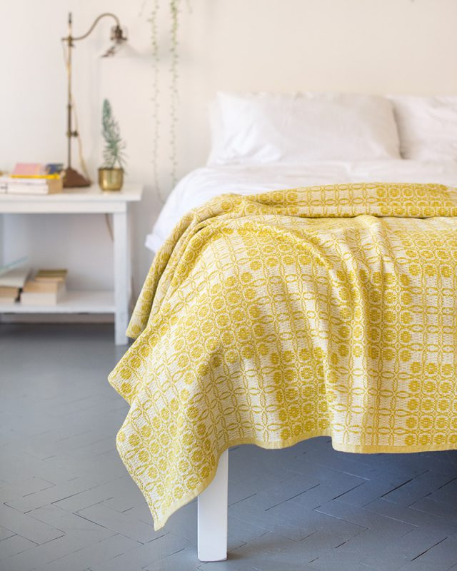 A Mungo Juno Cotton Blanket Throw in Mustard, pictured here in a bedroom scene, is a textile woven with all natural fibres at our mill in Plettenberg Bay, South Africa.
