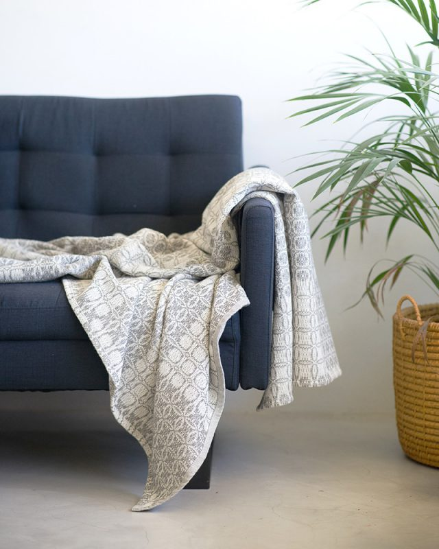 A Mungo Juno Cotton Blanket Throw in Grey, pictured here in a lounge scene, is a textile woven with all natural fibres at our mill in Plettenberg Bay, South Africa.