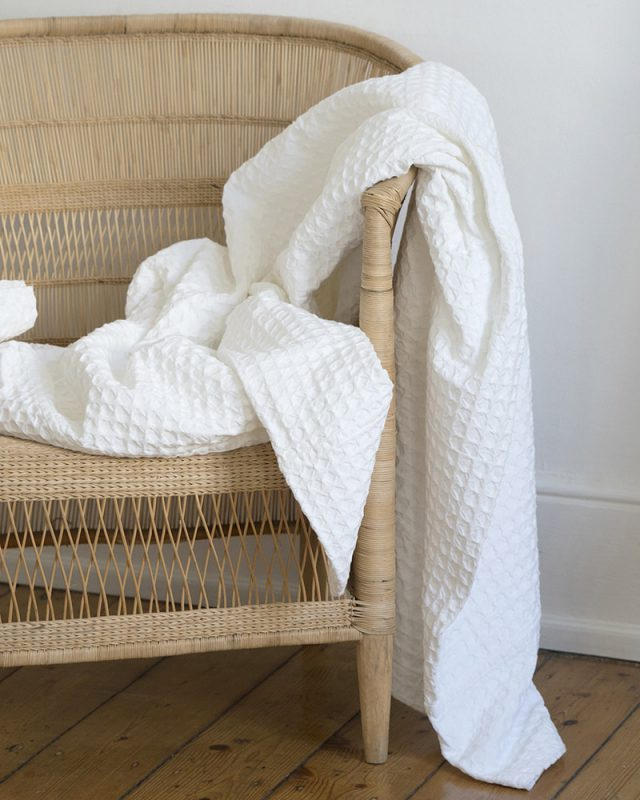Mungo Lattice Weave Blanket draped over a chair. pure cotton white bedcovers.