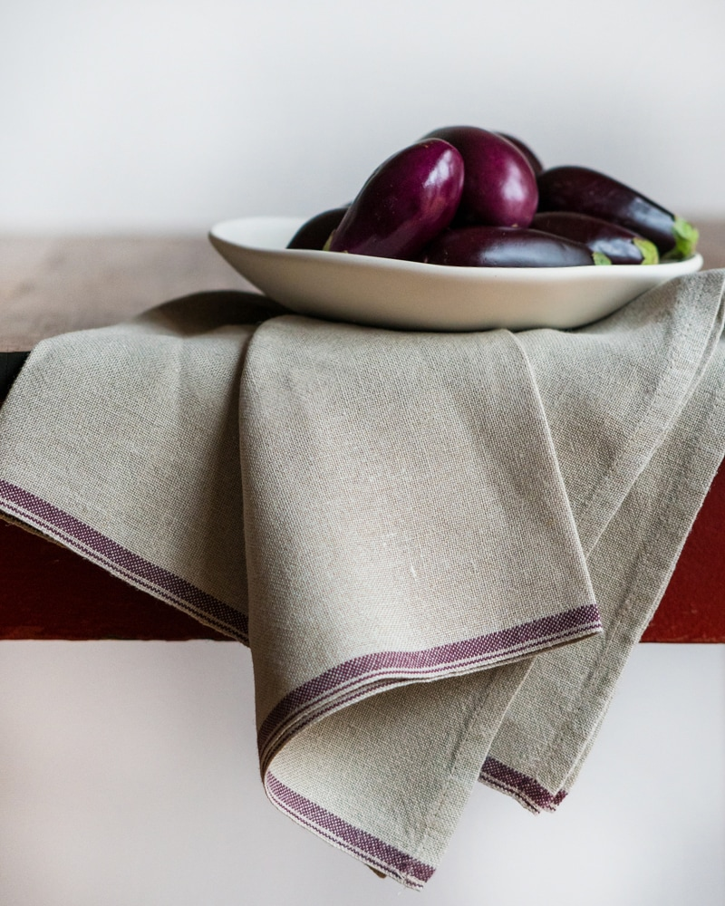 Flax Selvedge Napkins with an Aubergine stripe that runs along the true selvedge, woven at the Mungo Mill on antique Ruti looms