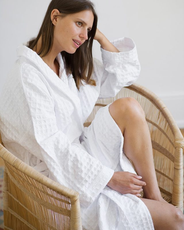 Woman on a chair wearing an all natural fibre Mungo Kamma Cotton Gown in textural White Lattice weave