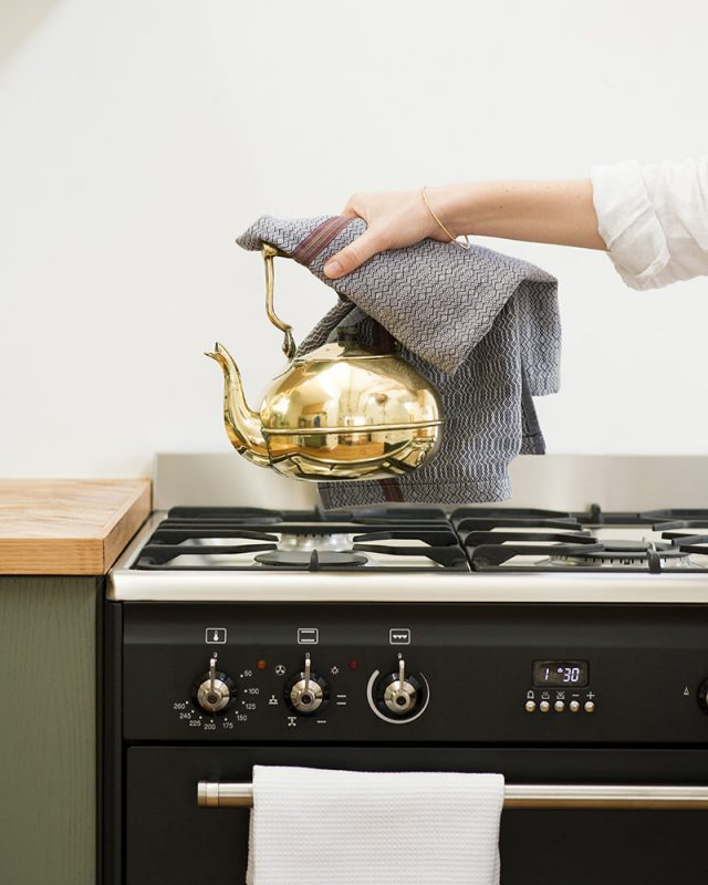 Hand holding a Mungo Kitchen Linen Boma Cloth in White Sand and a gold tea kettle over a gas stove.