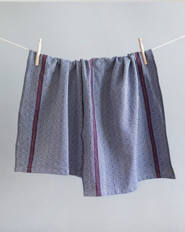 Mungo Linen Kitchen Boma Cloths in White Indigo hung with pegs from a clothes line.  Made with all natural fibres on the looms at our mill in Plettenberg Bay.