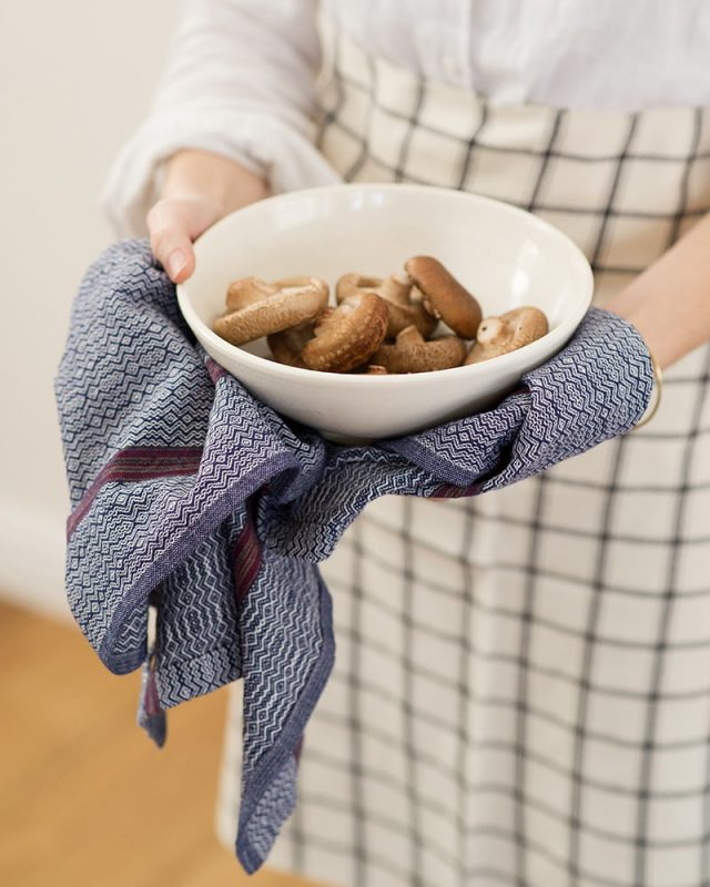 Cook hands holding a Mungo Linen Kitchen Boma Cloth in White Indigo and a bowl of brown mushrooms.