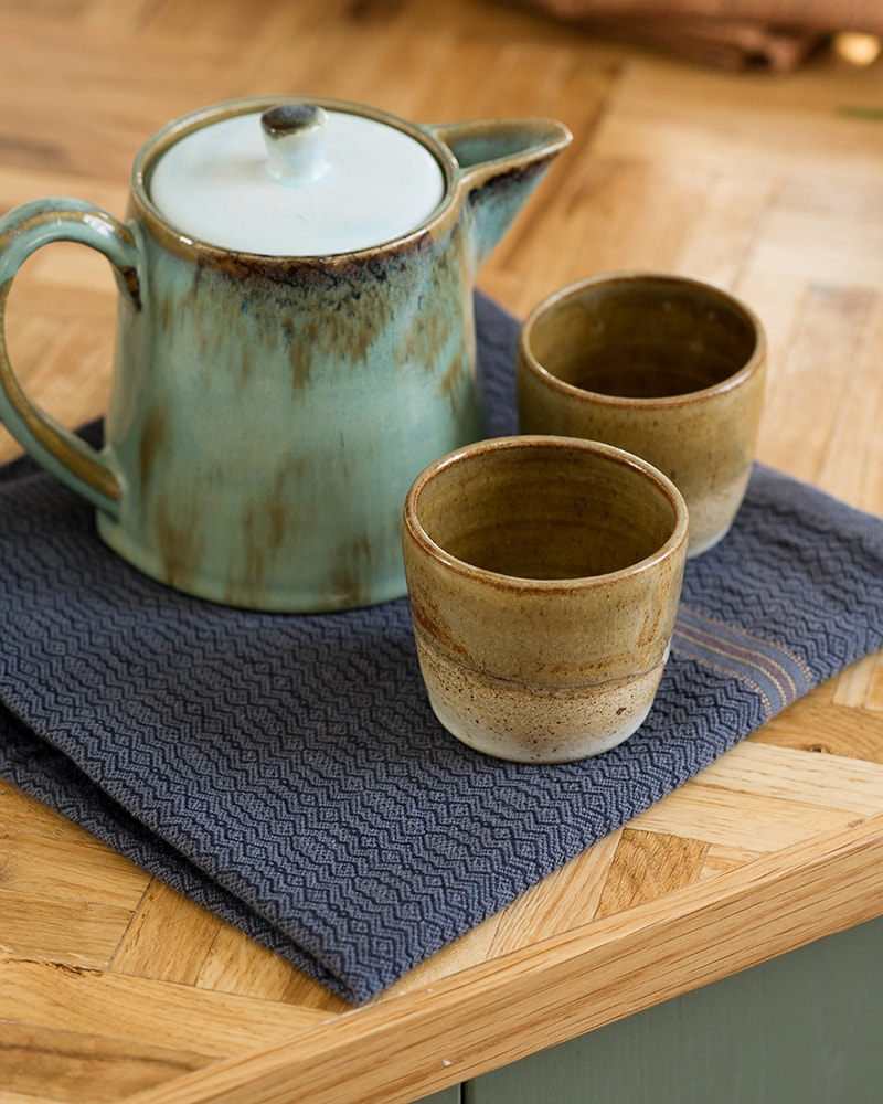 The Mungo Kitchen Linen Boma Cloth in Black Indigo, on a wooden counter with teapot and cups.
