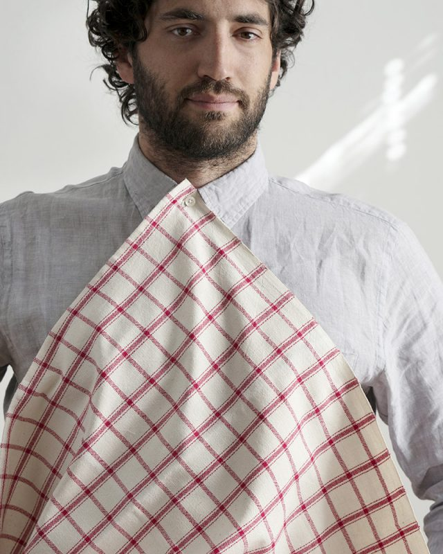 Man wearing a Mungo Apparel Cook's Cloth in Tomato Red as a napkin bib. Made with all natural fibres on the looms at our mill in Plettenberg Bay, South Africa.