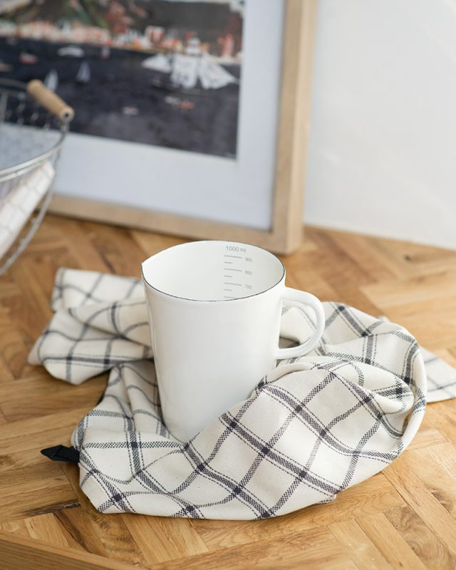 The Mungo Apparel Cooks Cloth in Charcoal on Natural, featured in a kitchen scene with a white beaker.