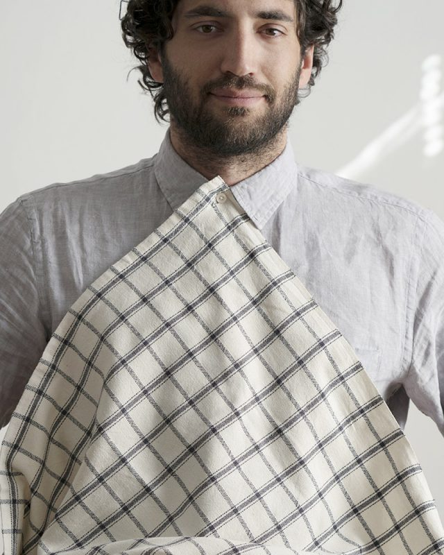 Man wearing a Mungo Apparel Cook's Cloth in Charcoal on Natural as a napkin bib.
