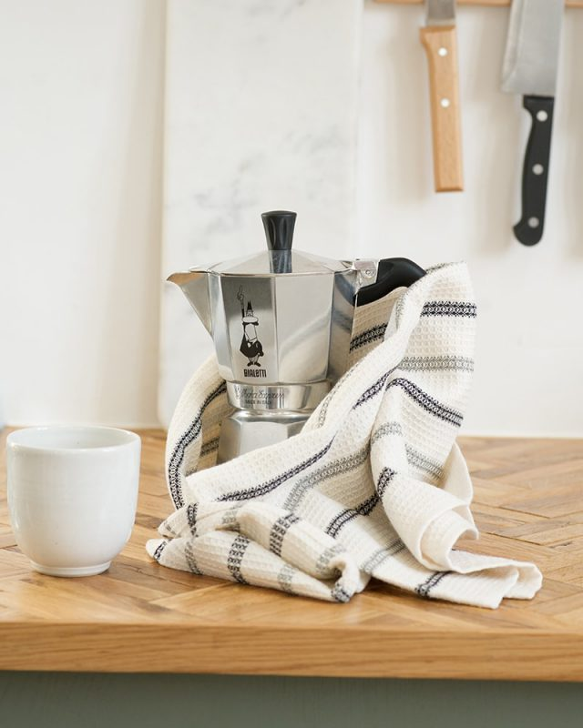 The Mungo Linen and Cotton Waffle Weave Kitchen Towel in Black and Grey Stripe, pictured in kitchen with a Bialetti and mug,