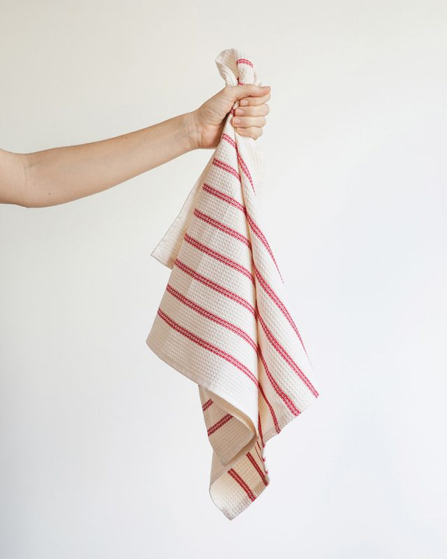 A hand holding the Mungo Linen and Cotton Waffle Weave Kitchen Towel in Red Stripe.
