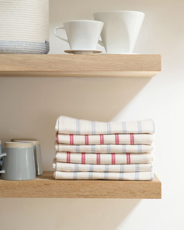 Mungo Linen and Cotton Waffle Weave Kitchen Towels in Lavender and Red Stripe, stacked on kitchen shelves with ceramic white mugs.