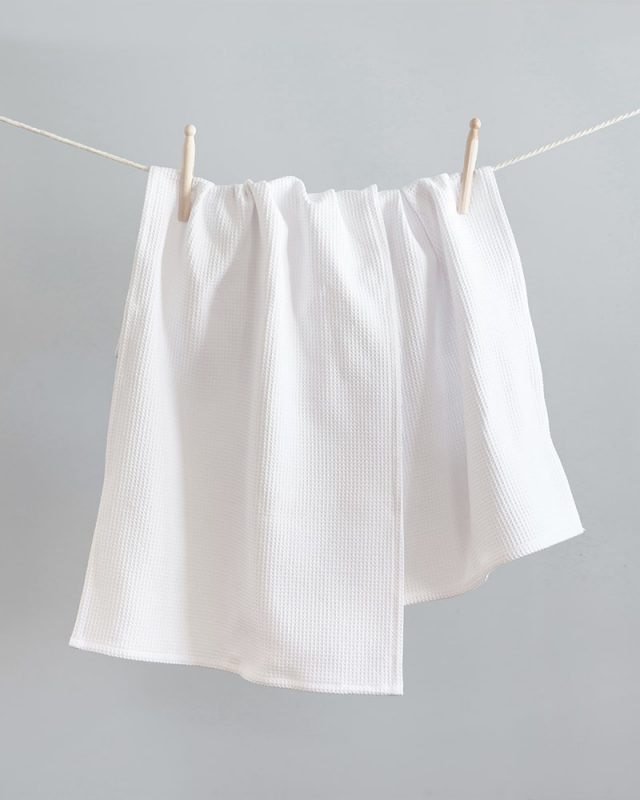 The Mungo Kitchen Linen Cotton Tea Towel in White, hung with pegs on a clothes line.  Made with all natural fibres on the looms at our mill in Plettenberg Bay.
