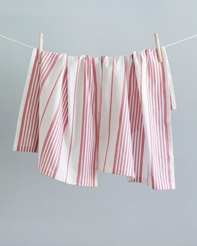Mungo Linen Kitchen Country Glass Cloths in Red Ribbon, hanging with pegs on a clothes line. Made with all natural fibres on the looms at our mill in Plettenberg Bay.