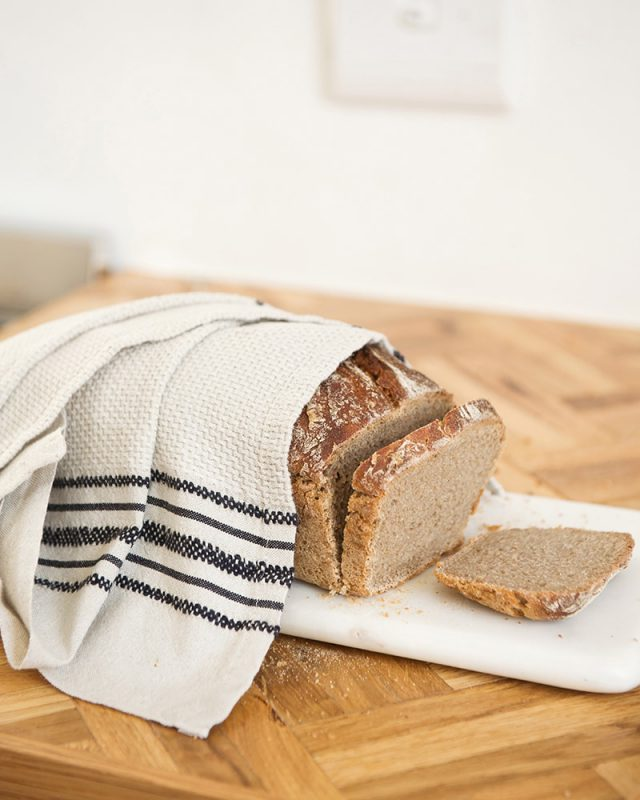 A Mungo Linen Kitchen Utility Cloth in Natural, on a wooden country table with fresh bread.