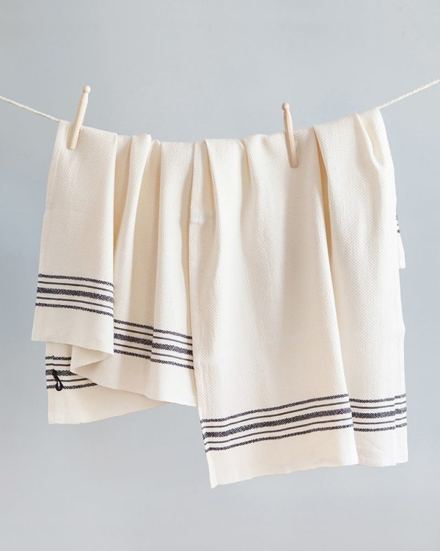 The Mungo Linen Kitchen Utility Cloths in Ecru, hung with pegs on a washing line. Made with all natural fibres on the looms at our mill in Plettenberg Bay.