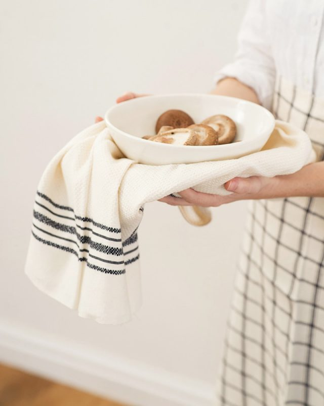 Cook hands holding a Mungo Linen Kitchen Utility Cloth in Ecru and a bowl of brown mushrooms.