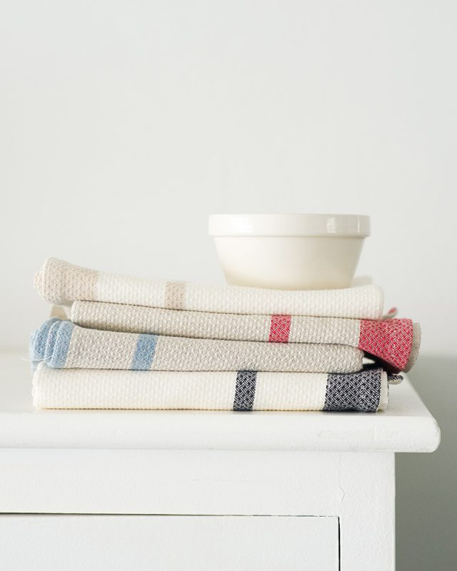 Mungo Huck Linen Kitchen Towels showing weave detail, stacked and folded with a white bowl on a cupboard.  Made with all natural fibres at our mill in Plettenberg Bay.