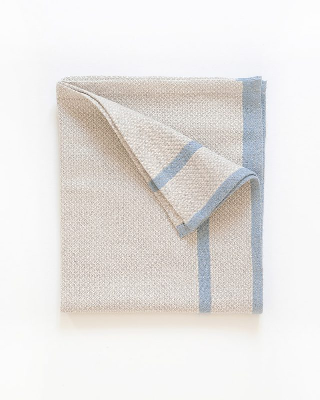 The Mungo Huck Linen Kitchen Towel in Bluebell on Natural, folded in a square. Made with all natural fibres at our mill in Plettenberg Bay.