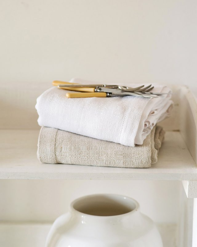The Mungo Cloverleaf Linen Table Cloth folded in Natural Flax and White on the shelf of a country kitchen.