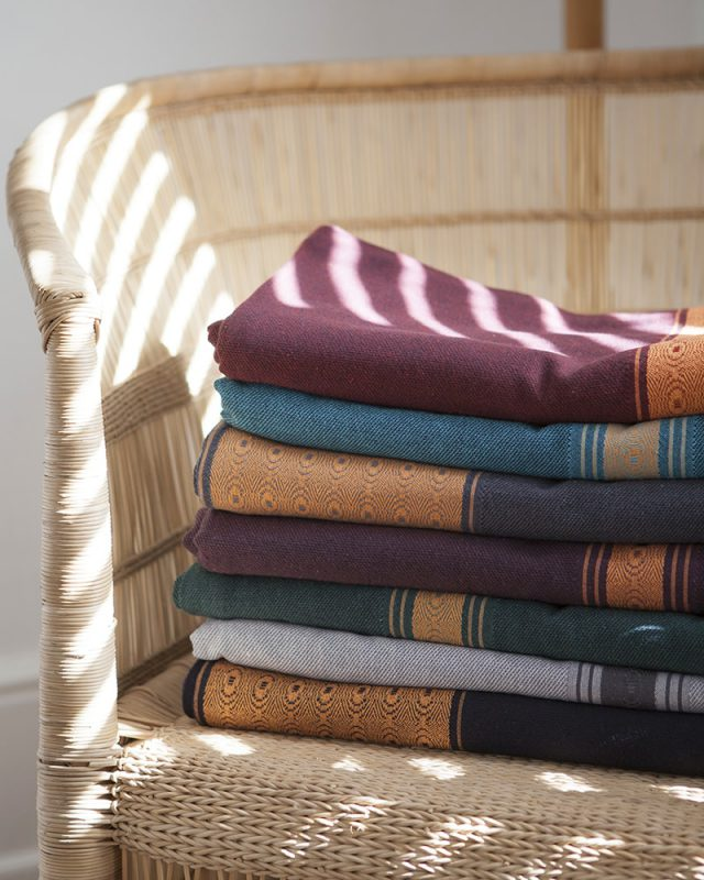 Mungo Linen Ottertrail Table Cloths in Hut, Sunset and Tidal, stacked and folded on a Malawian chair.