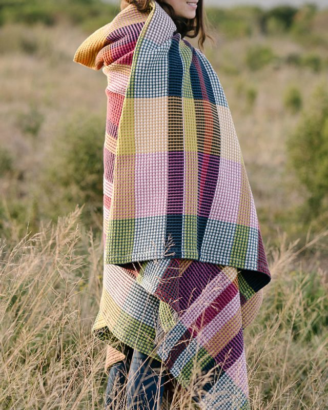 The Mungo Vrou-Vrou blanket in magenta wraps cozily to keep you warm in all conditions.