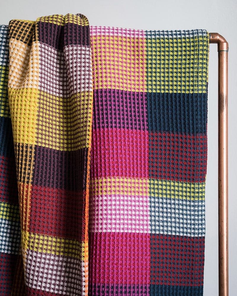 The Mungo Vrou-Vrou blanket is woven at the Mungo mill in Plettenberg Bay. Seen here in the Magenta colourway.