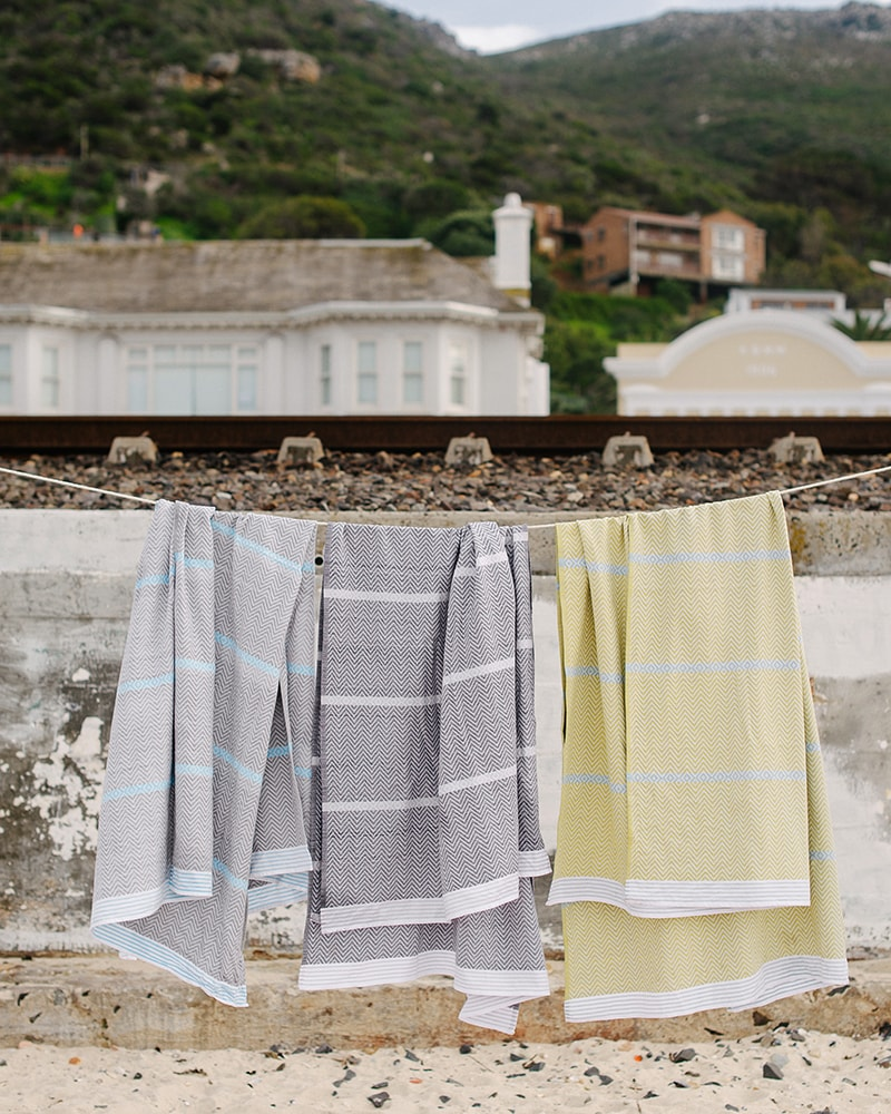 Three Mungo Tawulo Towels hanging on a line at the beach