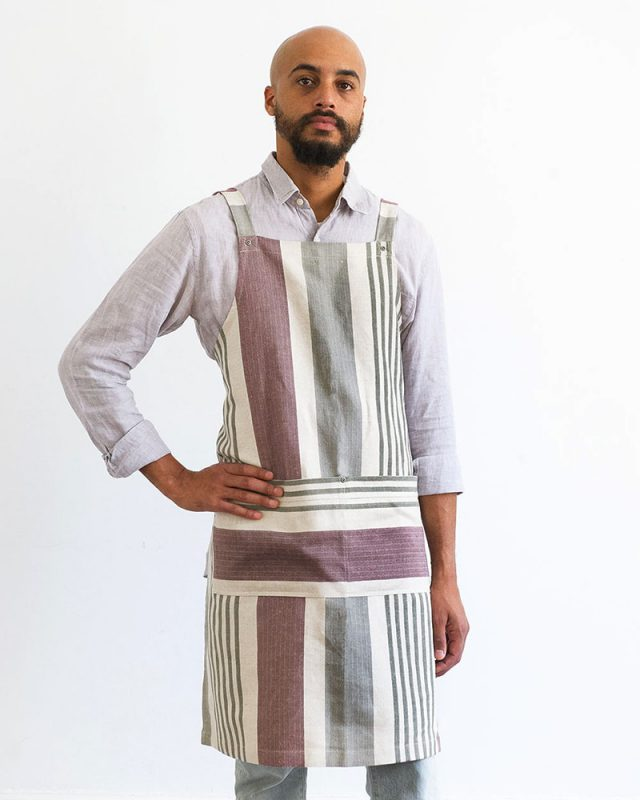 Model wearing the Mungo Chef's Apron in Aubergine, woven at our mill in Plettenberg Bay, South Africa
