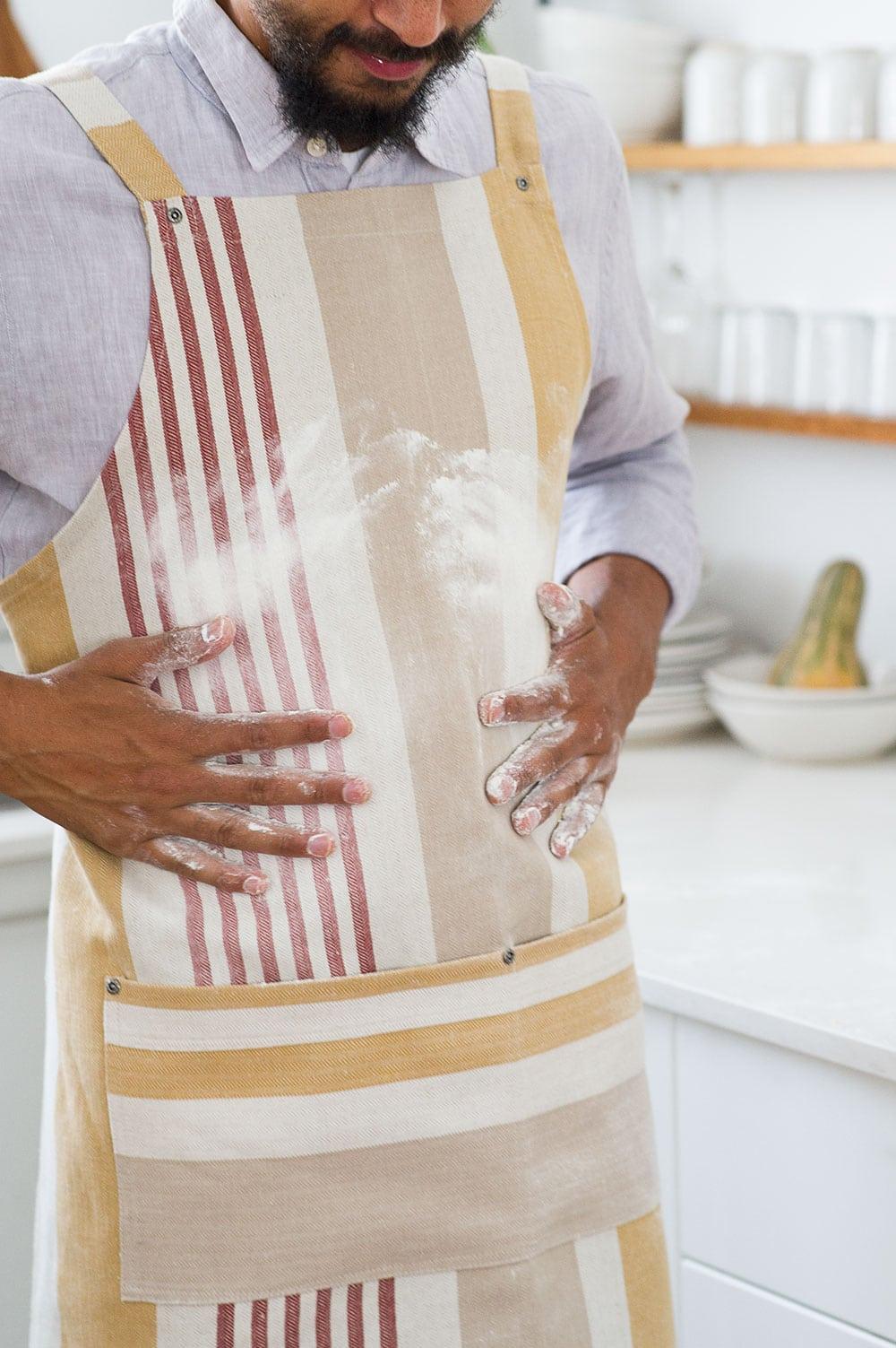 Mungo Chef's Apron in Yam, in a kitchen scene.