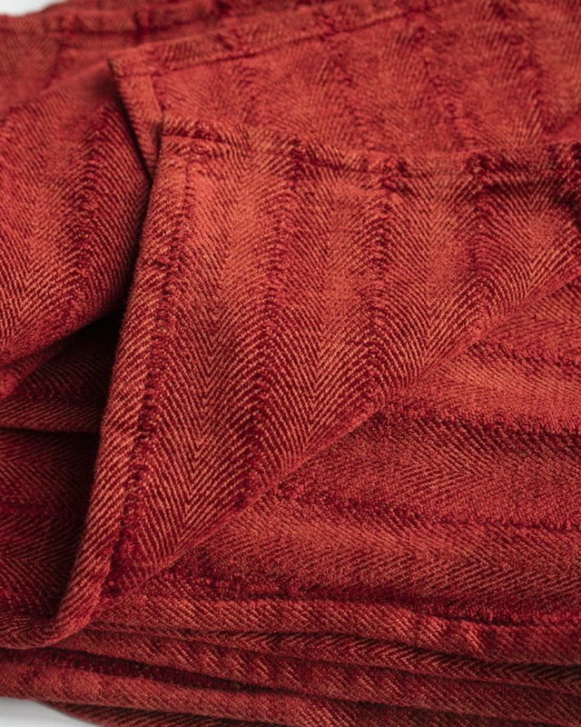 The Mungo Chenille Herringbone Throw in the Red colourway is woven at the Mungo mill in Plettenberg Bay from yarn dyed cotton