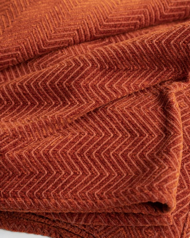 The Mungo Chenille ZigZag Throw in the Namib Orange colourway is woven at the Mungo mill in Plettenberg Bay from yarn dyed cotton