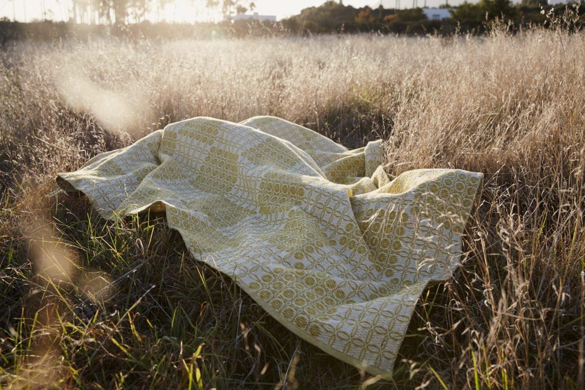 The Mungo Juno Throw in mustard. Perfect for keeping warm in winter