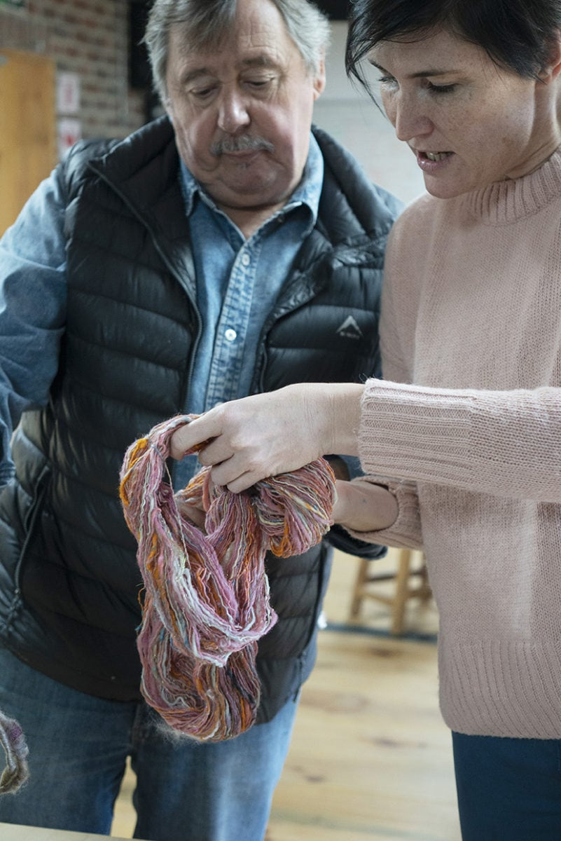 Mungo Master Weaver, Stuart Holding looking at the colourful handspun yarn of Mungo US's shop manager, Rachel Neil