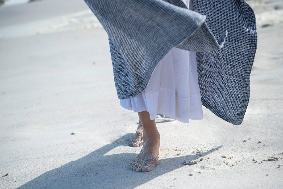 A day at Misty Cliffs beach with the Mungo Dhow Towel in Deep Sea colourway. A 100% linen towel designed, woven and made in South Africa